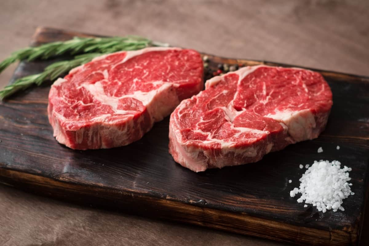 Two 1 inch thick ribeye steaks on a cutting board with rosemary and a pile of sea salt