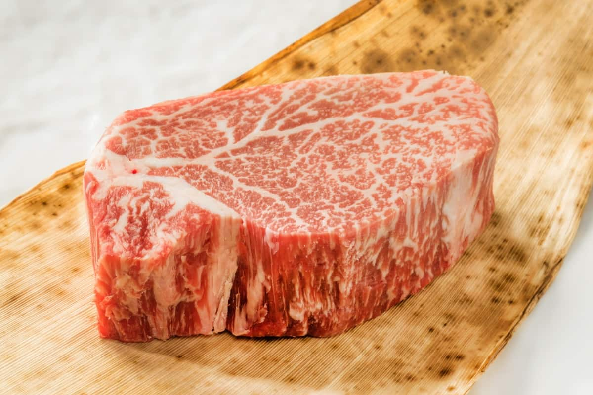 A 2 inch thick wagyu cross steak with intense marbling, on a cutting board on white background