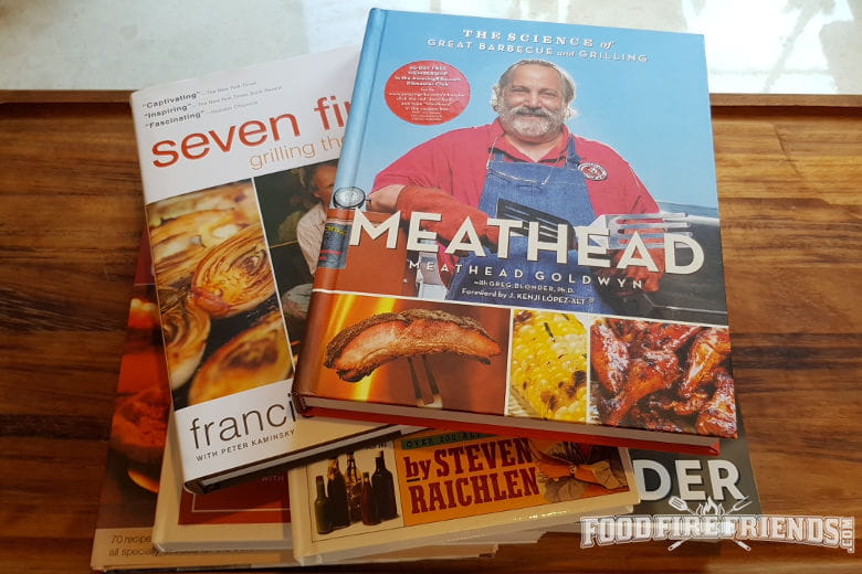 Some of the best bbq and grilling cookbooks piled on eachother on a table