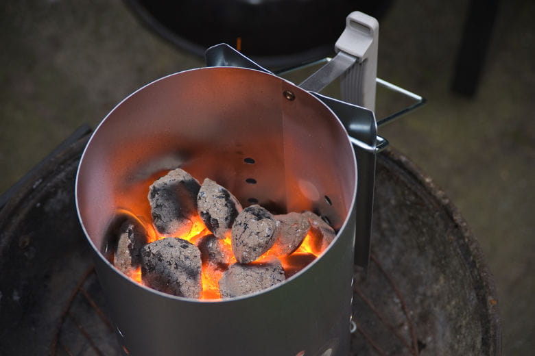 A charcoal chimney starter half full of hot burning coals