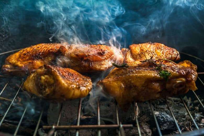 Browned chicken pieces on a grill with wispy smoke