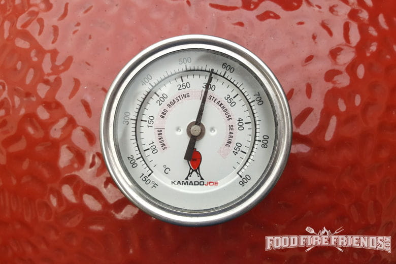 A temperature gauge showing 300 degrees c on a red Kamado Joe grill