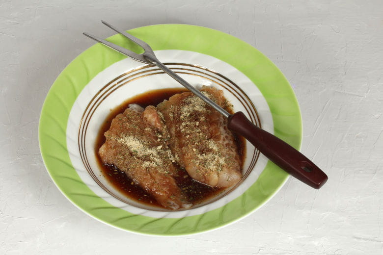 Some meat marinading in a bowl with a fork resting on the edge