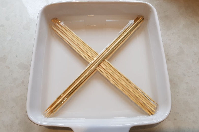 Some bamboo skewers soaking in a bowl