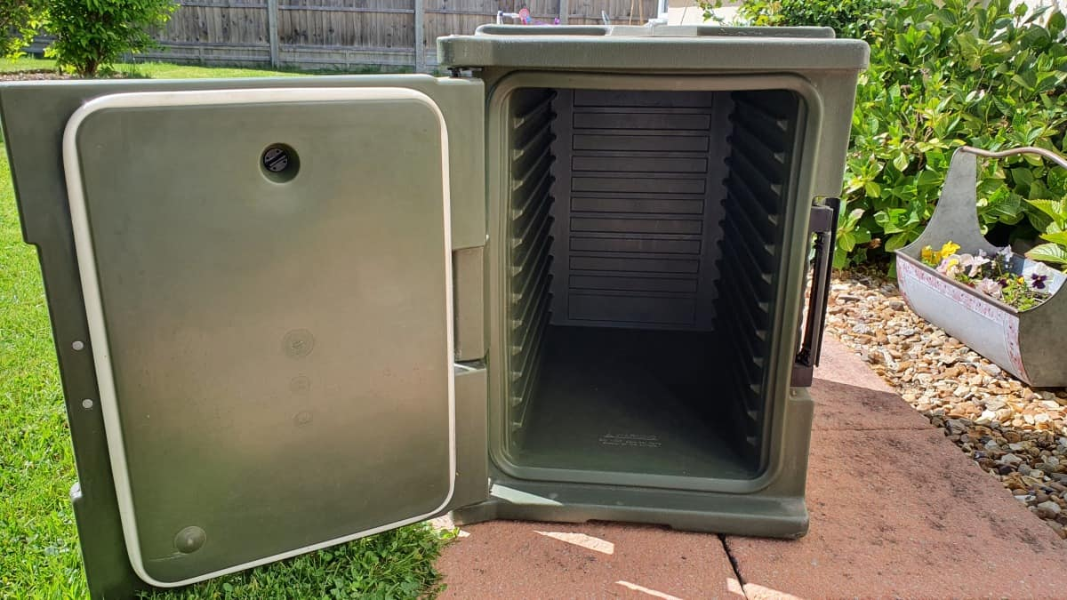 A green cambro food warmer with door open
