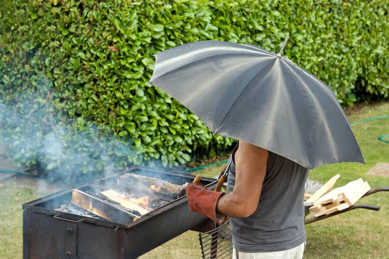 Man lighting a BBQ in the rain