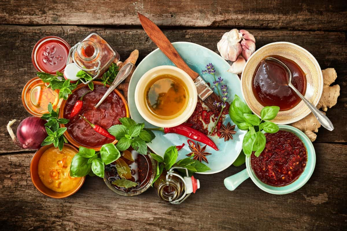 Top view of many different marinades and spices on a table