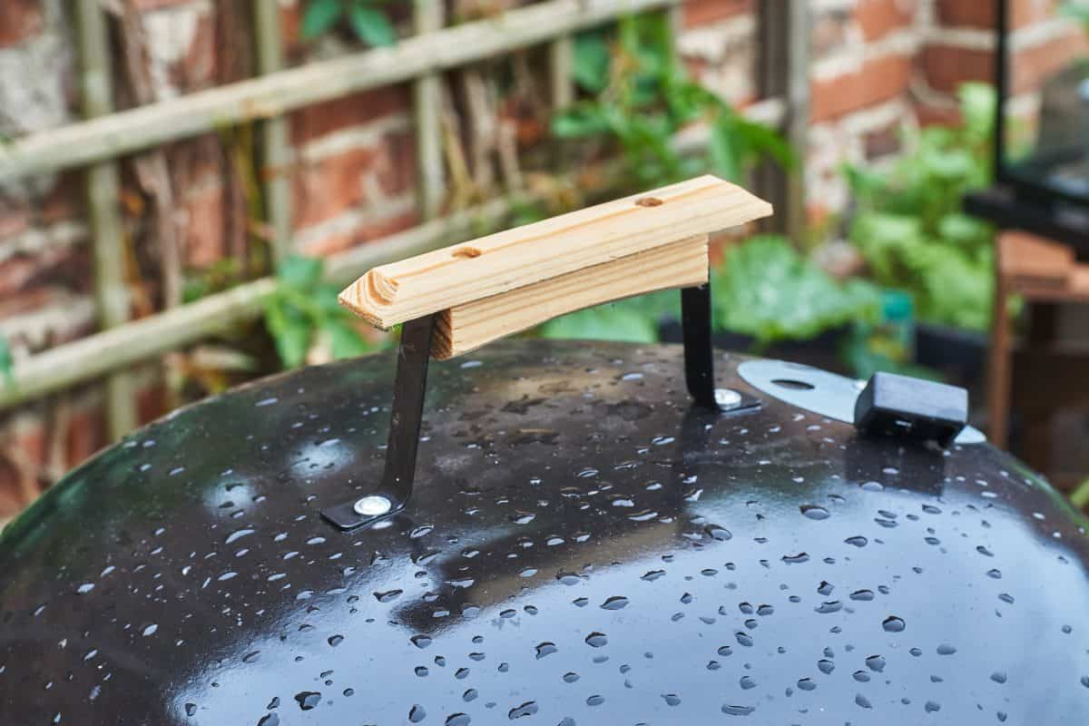 A charcoal kettle grill lid, with wooden handle, covered in rain