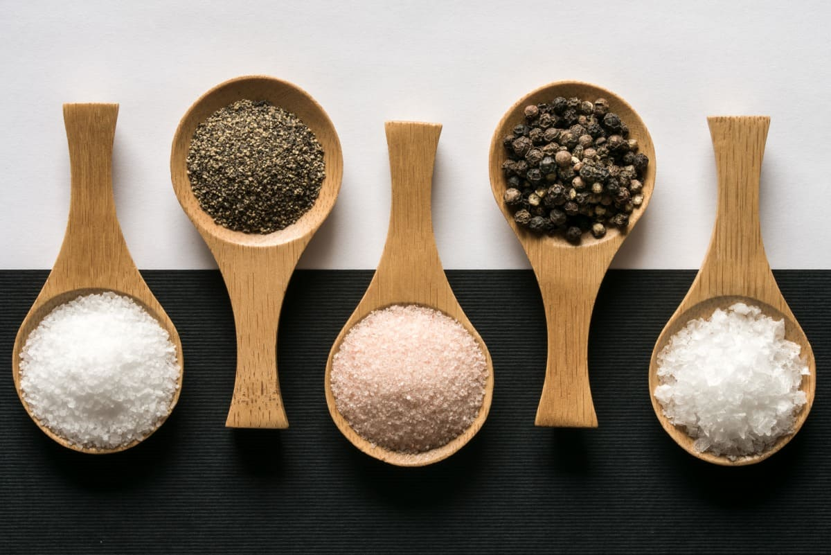 Kosher salt, ground pepper, himalayan salt, peppercorns, and sea salt flakes on wooden spoons on a black and white background