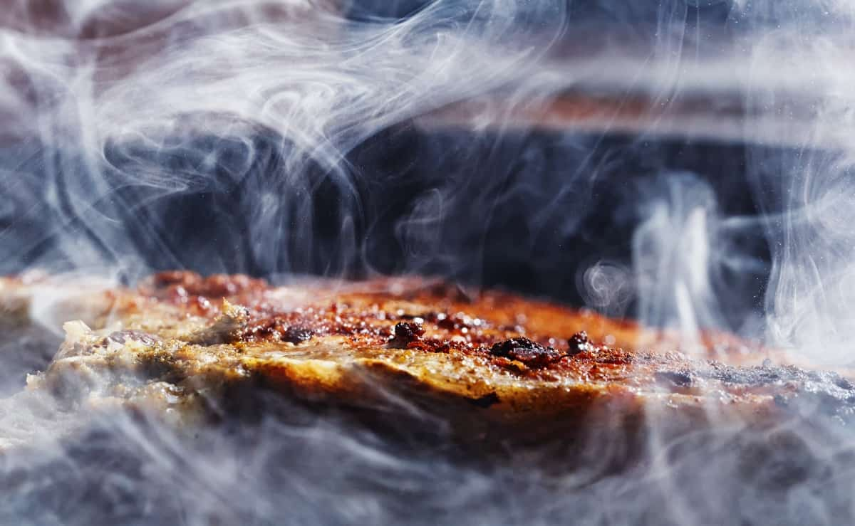 A small cut of pork being enveloped with rolling smoke