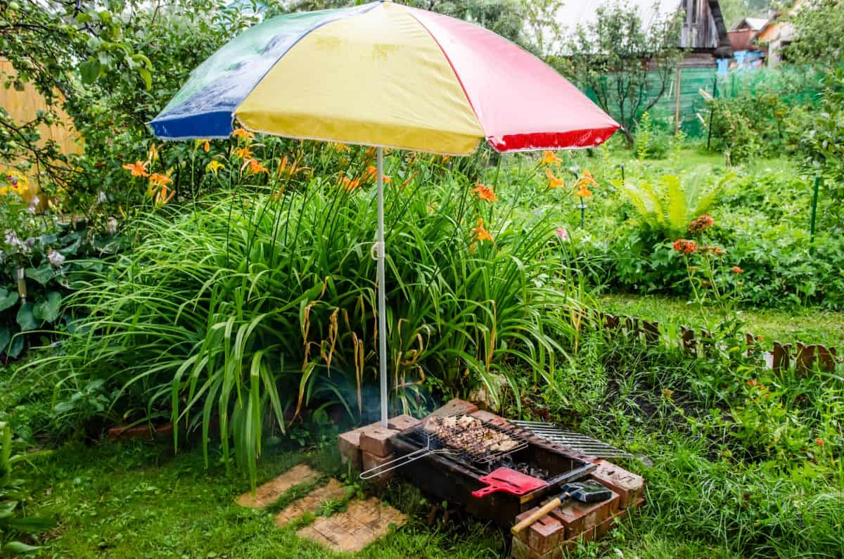 A patio umbrella over kebabs on a low grill in the rain