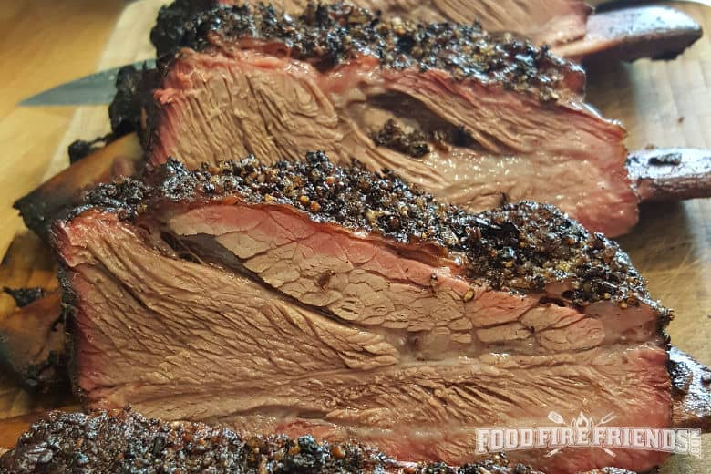 Close up of nice, moist beef ribs with a smoke ring and peppery rub crust