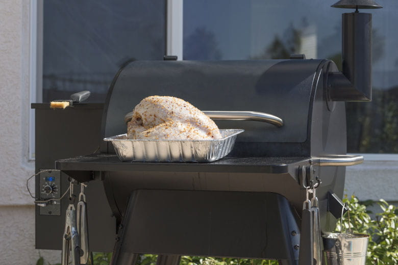 Poultry sitting on the front table of a pellet smoker, ready to be cooked