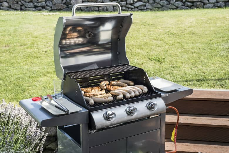 A 3 burner gas grill full of sausages and meats against a grass bg