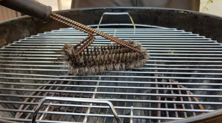 Stainless steel grill grates being cleaned with a wire brush