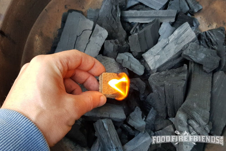 A firelighter being placed into a bed of lump charcoal