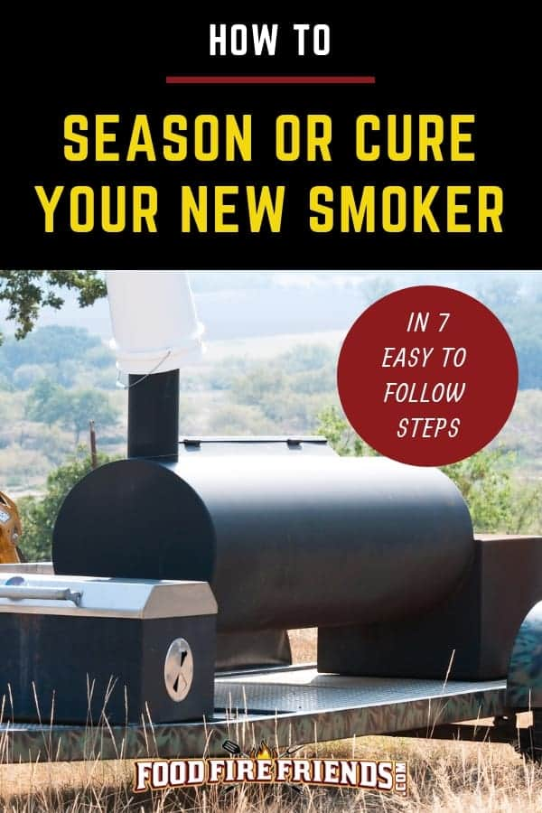 a large, new, offset smoker with smoke billowing from a chimney in a field