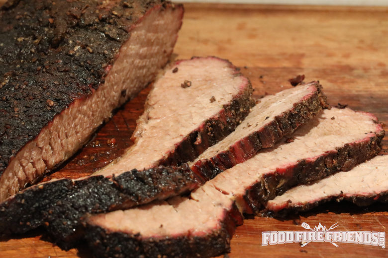 Sliced smoked brisket on a wooden chopping board.