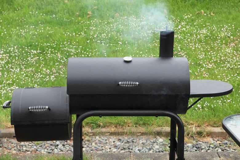 Close up of black offset smoker against grass background