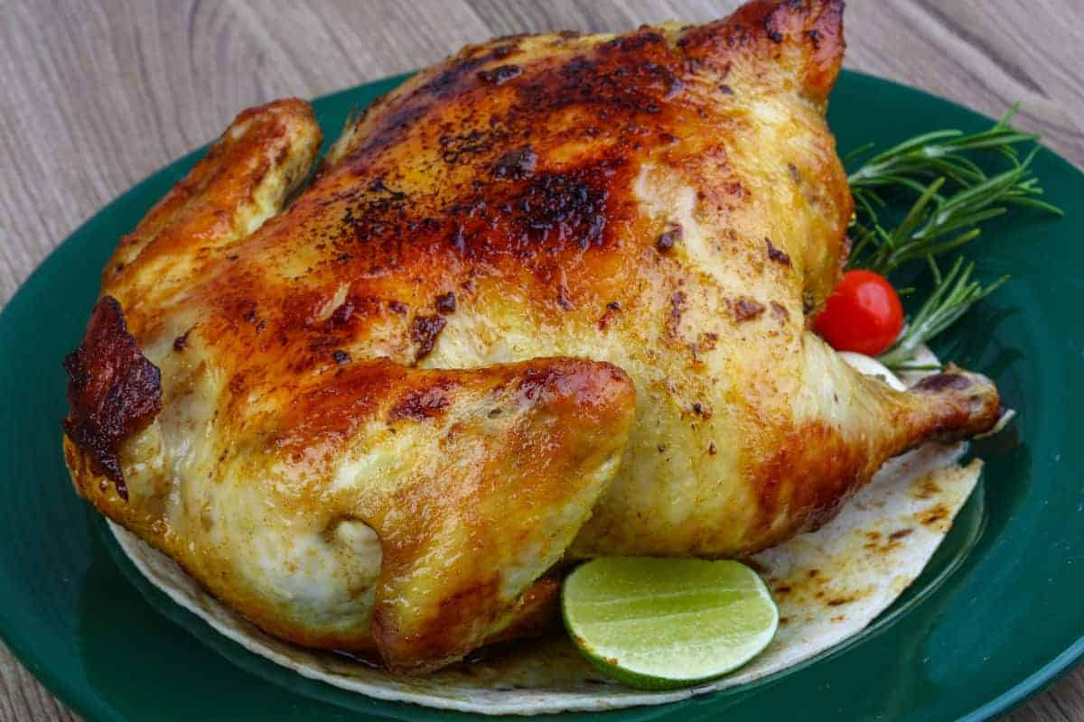 Grilled chicken with lovely crispy skin, on a green plate with tomatoes and half a lime