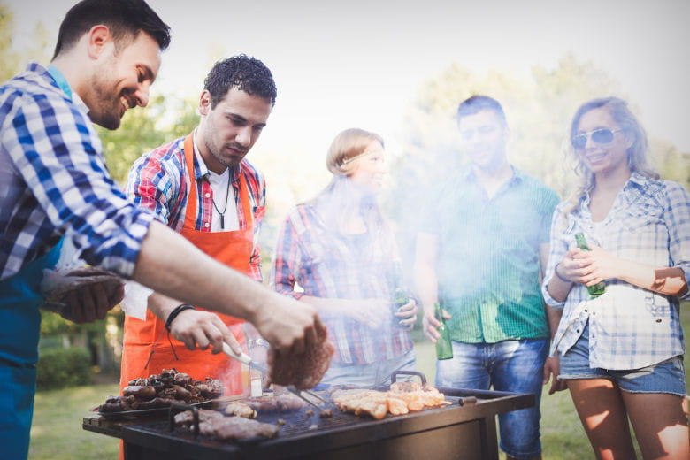 A grill party with friends gathered round a smoking BBQ laughing