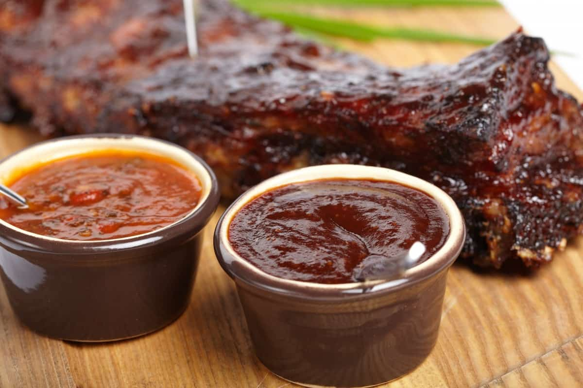 Two pots of bbq sauces in front of pork ribs