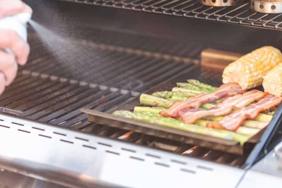 Water being sprayed onto flames to keep a bbqs heat down, with a tray of veg and bacon on the grill