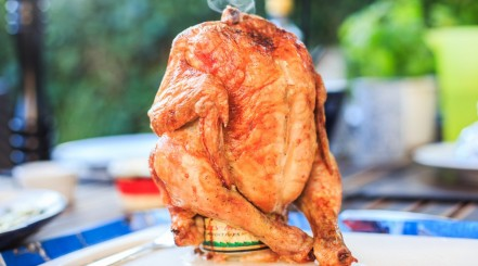 beer can chicken, grilled, sitting upright on a white cutting board with a blurred garden background