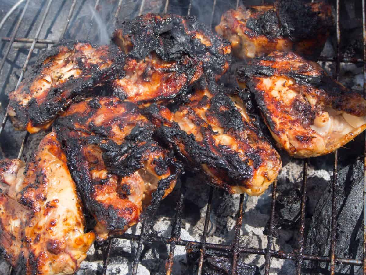 Burnt chicken pieces on a charcoal grill