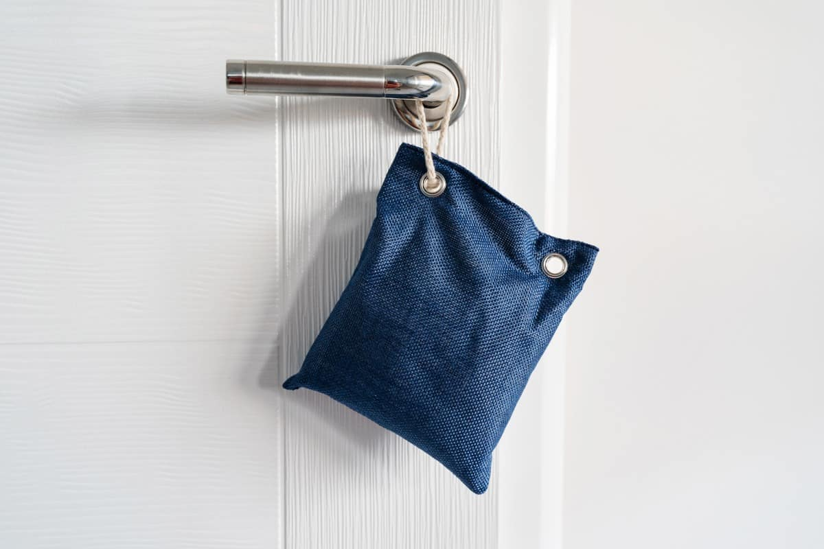 A denim bag holding charcoal hanging from a door handle