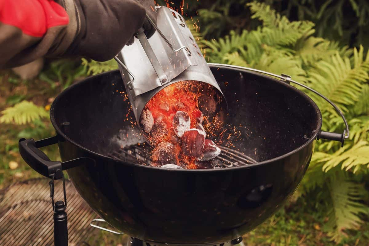 A man pouring lit coals from a chimney starter into a charcoal grill