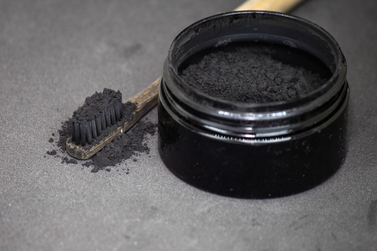 charcoal toothpaste in a small pot, and on a toothbrushes bristles