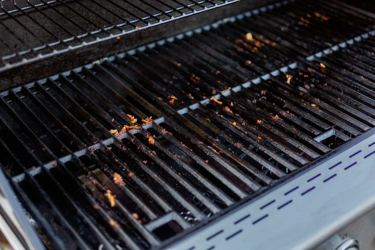 Close up of dirty gas grill cast iron grates