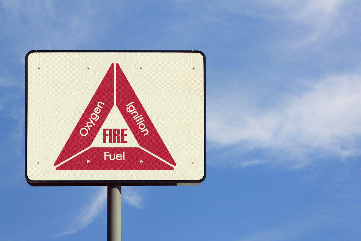 A road sign showing the fire triangle in red on a beige background