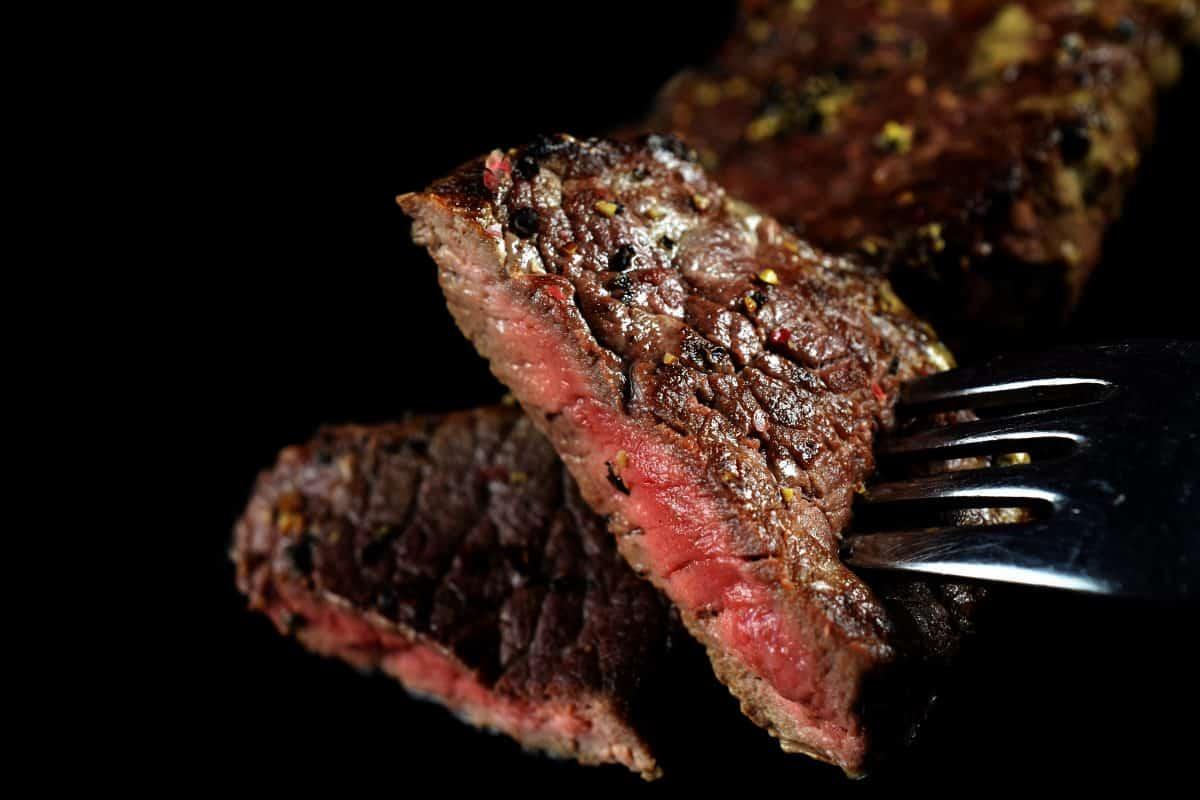 A fork full of medium rare steak