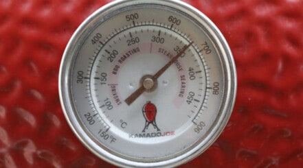 A temperature gauge showing 350 degrees c on a red Kamado Joe grill