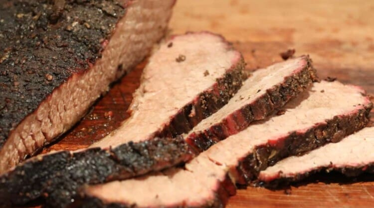 Sliced smoked brisket on a wooden chopping board