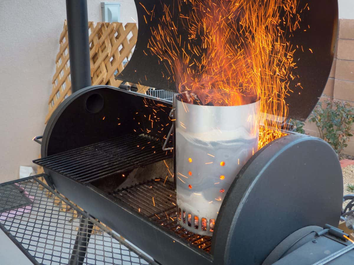 Sparks flying from a lit chimney starter sitting in a barrel type grill