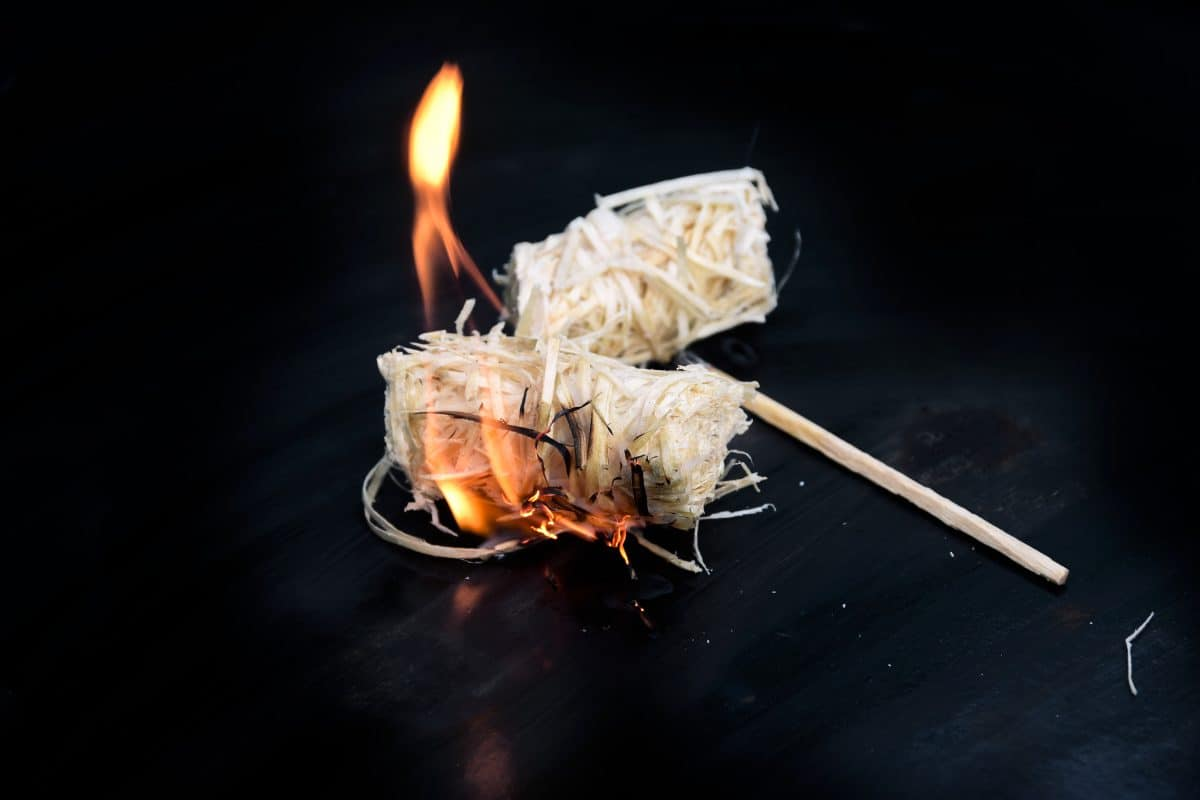 Two lit natural wood wool and wax firelighters on a dark background