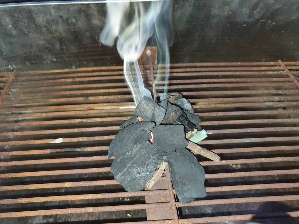 Using paper and kindling to light charcoal