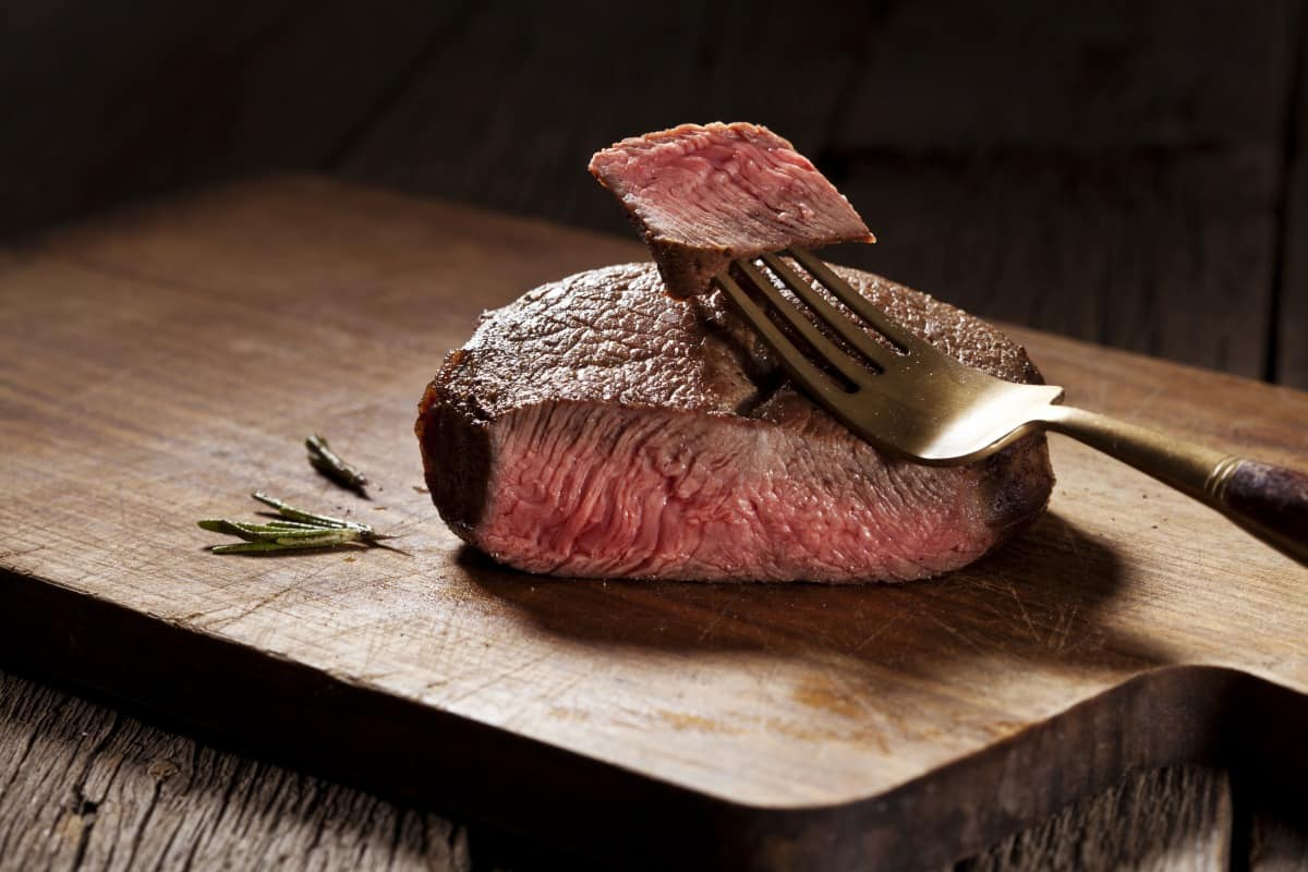 A rare filet steak, slice in half with a small piece on a fork showing how pink it is