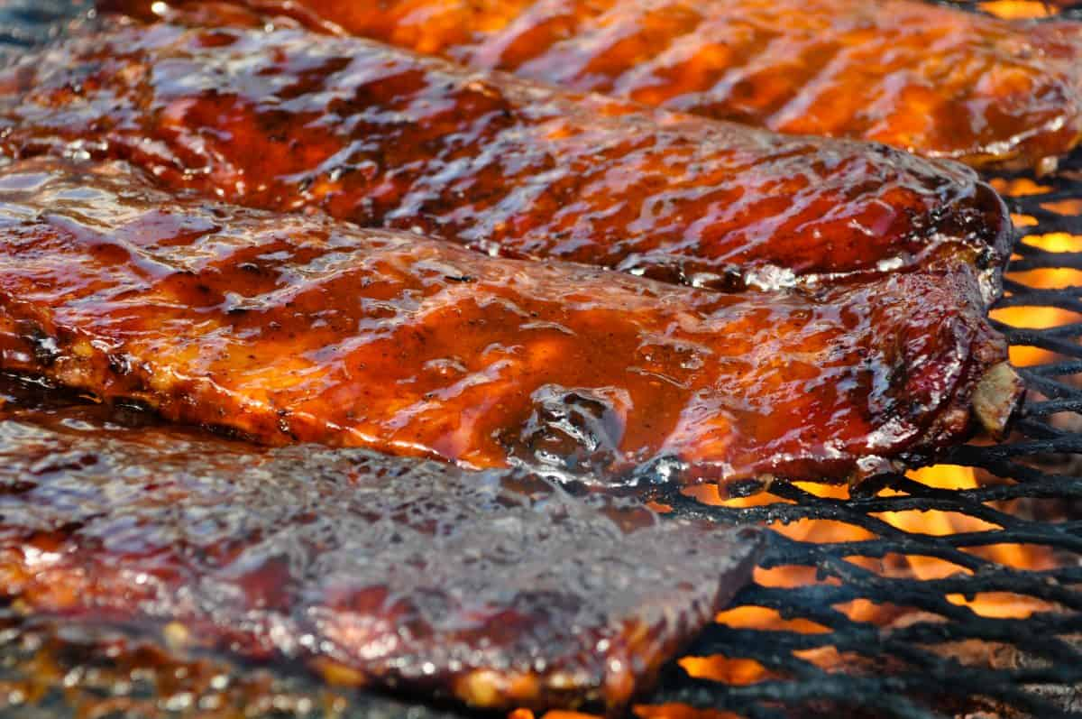 Three racks of ribs on a flaming charcoal grill