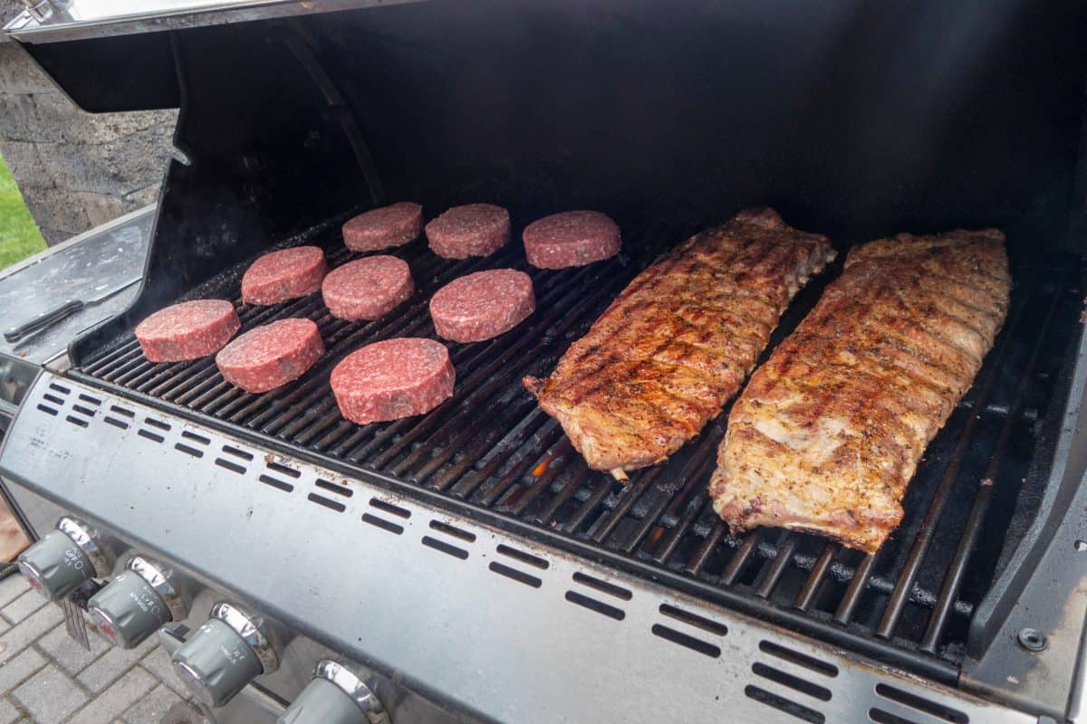 Pork ribs and beef burgers on a gas grill