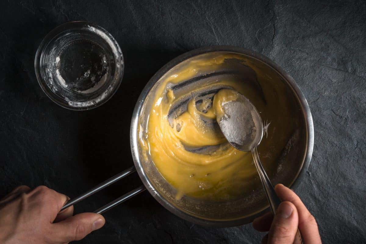 Making a roux with butter and flour: A pan and empty glass shot from above
