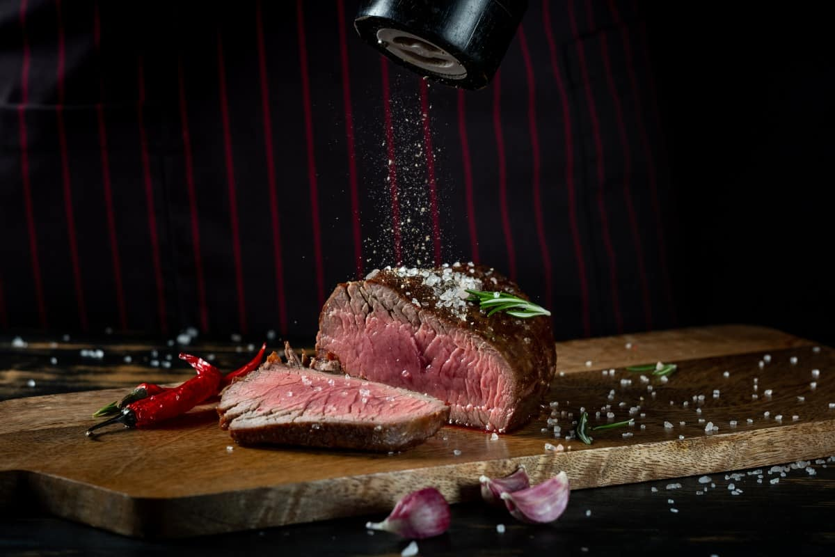 Salt being sprinkled onto a grilled filet mignon steak sliced in half, showing it's insides cooked to rare