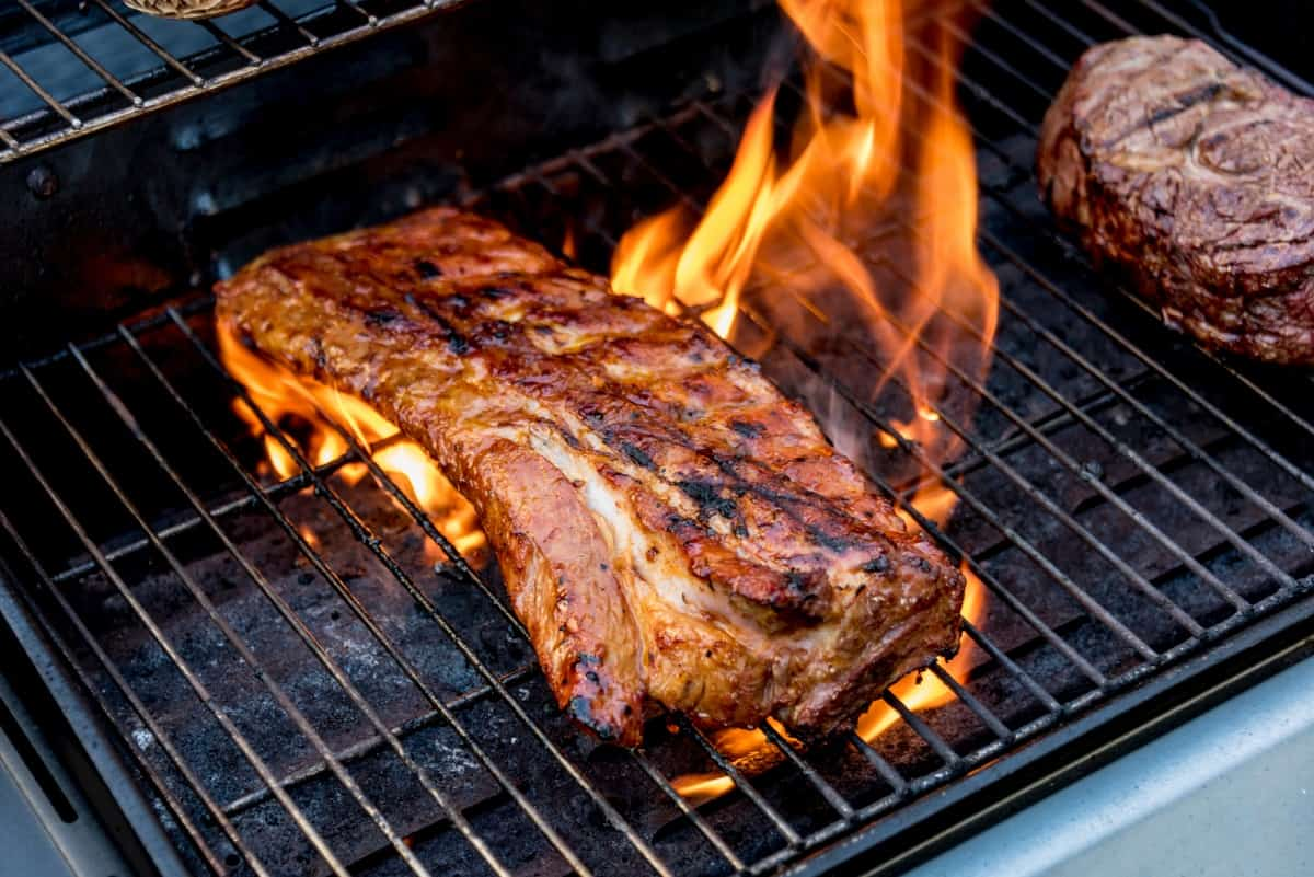 Searing a large piece of pork on a flaming hot grill