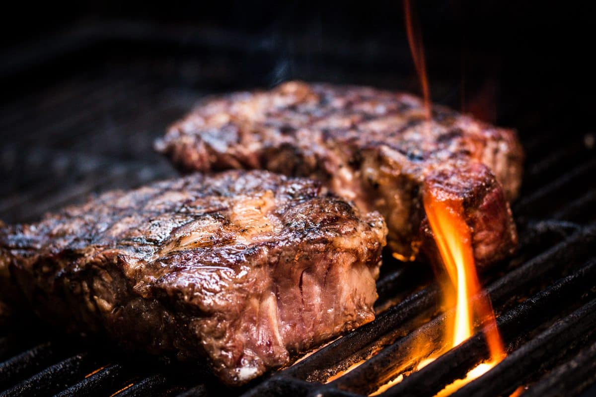 searing steak on a charcoal grill