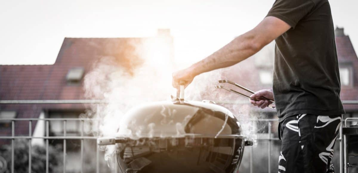 A man holding the lid on a smoking charcoal grill