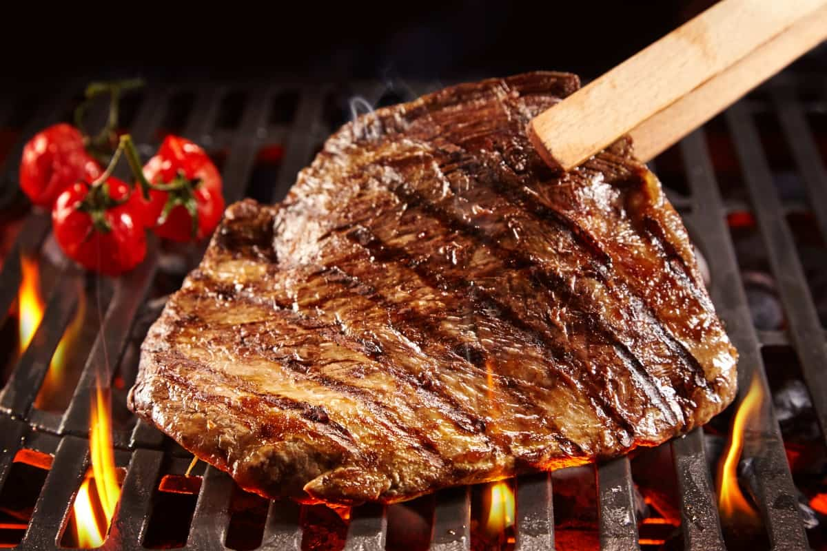 Turning a steak on a hot grill with a pair of wooden tongs