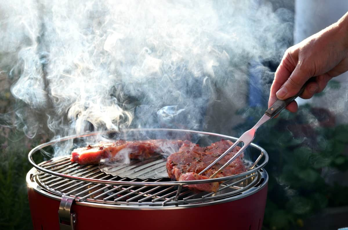 A man turning meat with a bbq fork on a small, round, smoking bbq